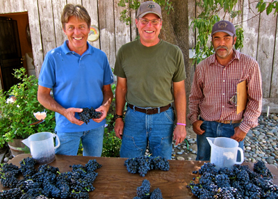 Jessie's Grove's Greg Burns (left), showing off mix of grapes (Zinfandel, Carignan and Black Prince) from Royal Tee Vineyard (planted 1888)