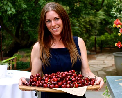 Lodi Visitor Center's Gina Licari shows off just-picked Harney Lane Winery grown Bing cherries at pre-ZinFest event