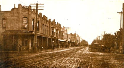 The  first buildings next to the Central Pacific Railroad stop; at the corner of the unpaved Sacramento and Pine Streets, around the time when the town's name was changed to Lodi in 1874