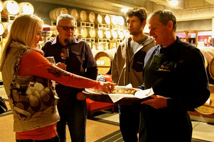 Wine lovers enjoying treats and service in LangeTwins barrel room…
